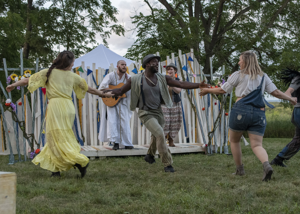 three actors dancing, two white women and one Black man and one white man playing a guitar in the background during a production of As You Like It
