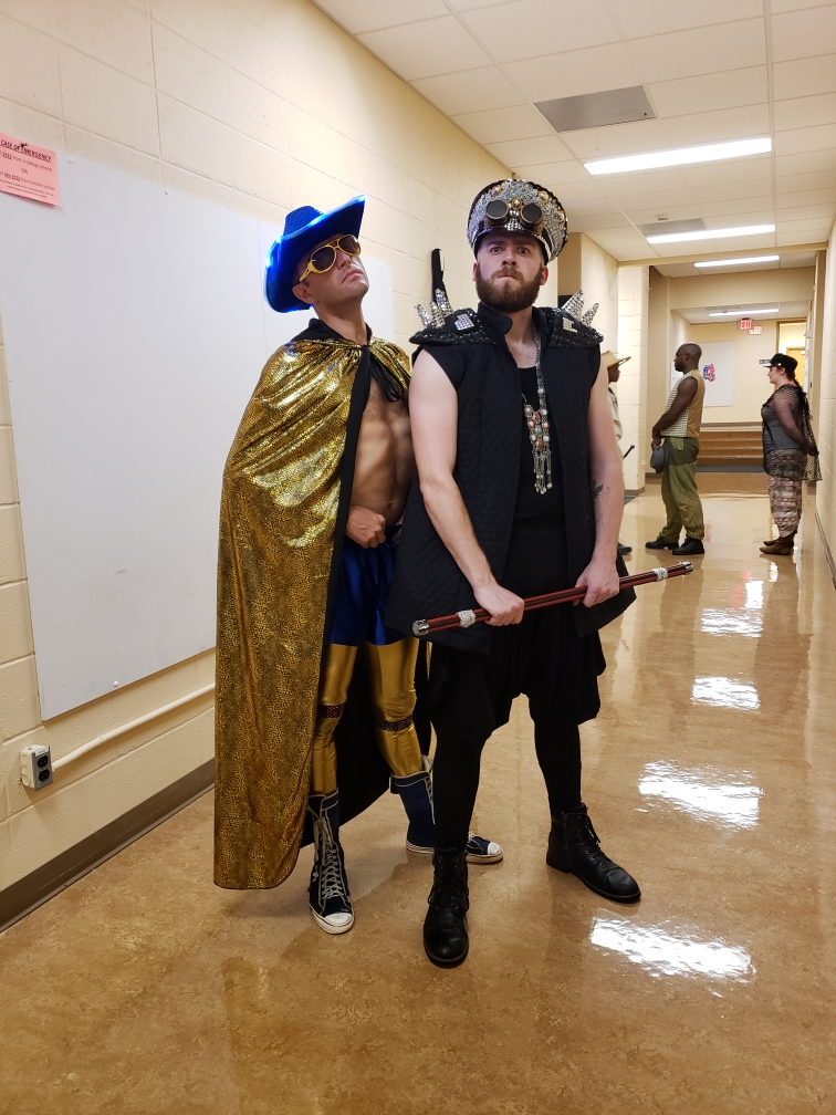 Two white males standing next to each other in a hallway. One is wearing a gold cape with a blue cowboy hat. The other is wearing a black outfit.