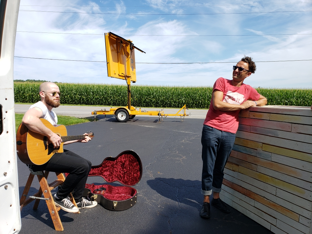 One white male sitting playing guitar and one white male standing leaning up against a platform sitting outside with a cornfield behind them